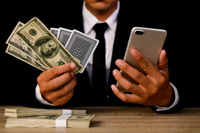 Businessman Gambling With Phone & Cash