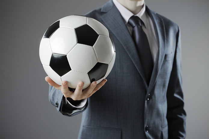 Businessman Holding Out Football