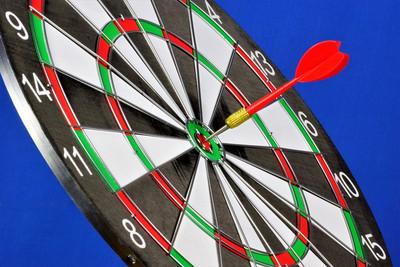 Dartboard with Dart in Bullseye on a Blue Background