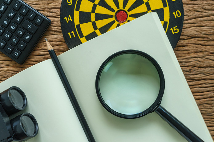 Dartboard with Magnifying Glass and Notepad