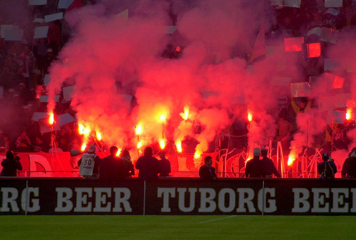 Football Fans Holding Red Flares
