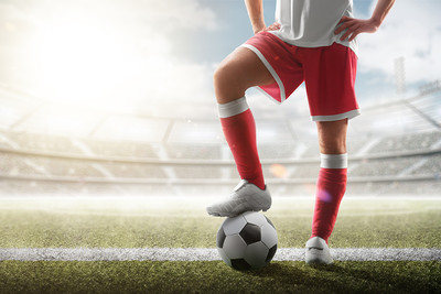 Football Player Standing on Ball