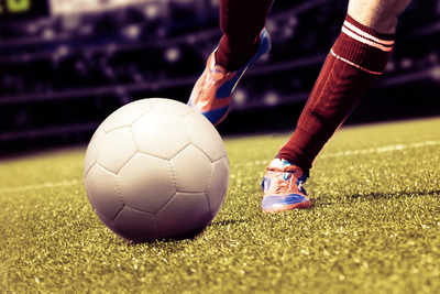 Footballer with Red Socks Striking Football