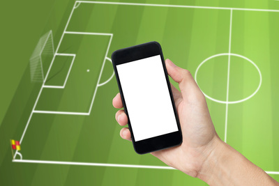 Hand Holding Mobile Over Football Pitch Graphic