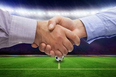Handshake over football pitch
