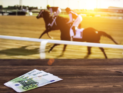 Money On Table with Horse Race in Background