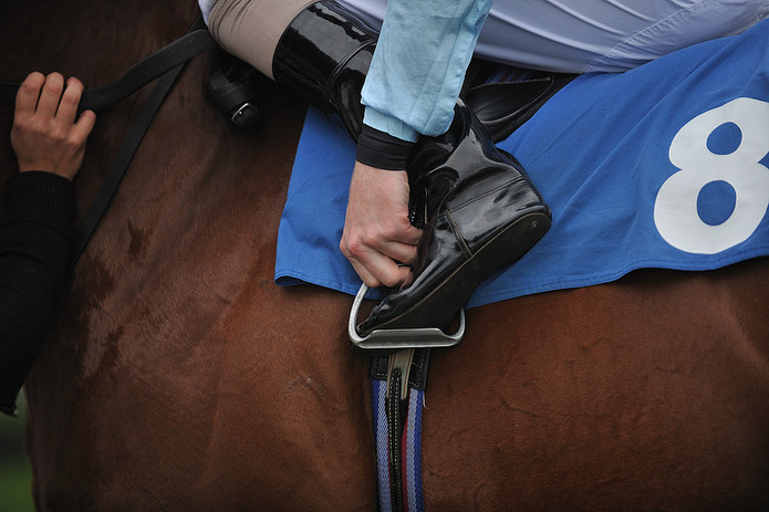 Jockey Putting Foot in Stirrups