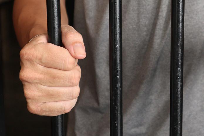 Man Holding Prison Bars