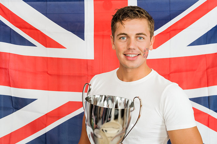 Man Holding Trophy in Front of British Flag