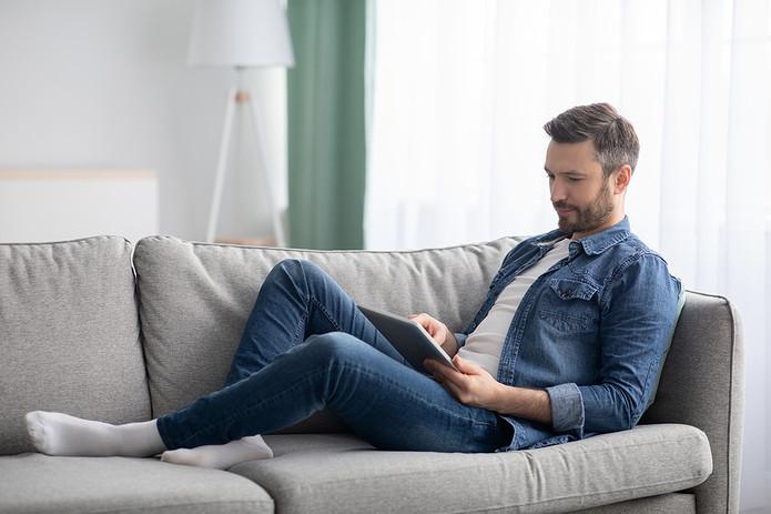 Man Watching Tablet on Sofa