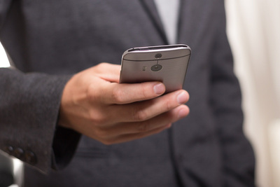 Man in Suit Holding Mobile Phone