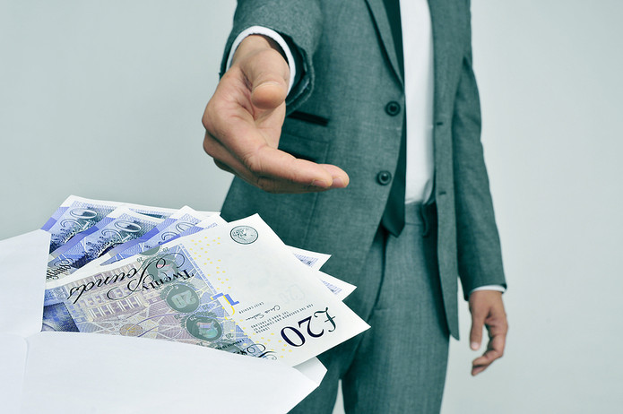 Man in Suit Taking Envelope of Money