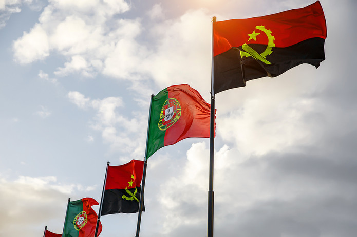 Portugal and Angola Flags Against Cloudy Sky