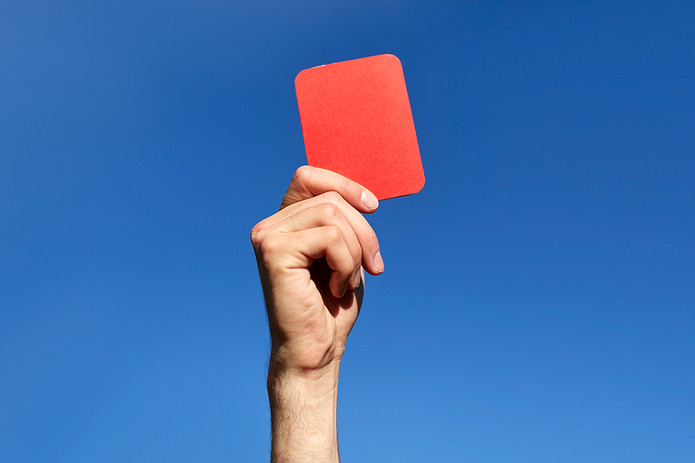 Red Card Held Against Blue Sky