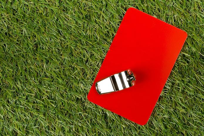 Red Card and Whistle on Grass