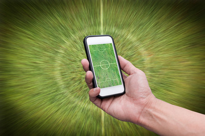 Smartphone Held in Front of Blurred Football Pitch