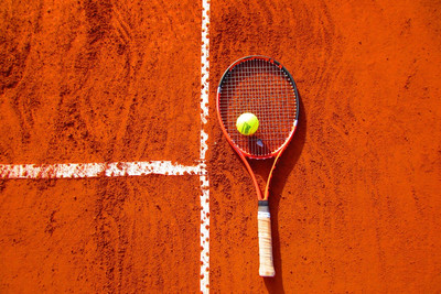 Tennis Racket on Clay Court