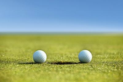 Two Golf Balls Near Hole