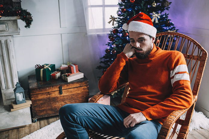 Unhappy Man Wearing Christmas Hat