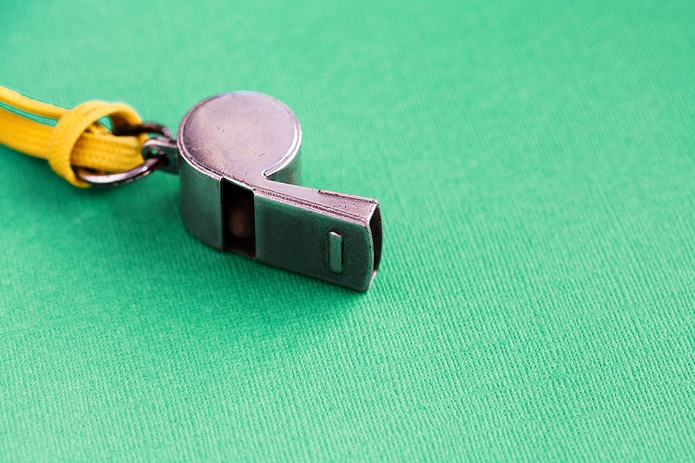 Vintage Football Whistle on a Green Background