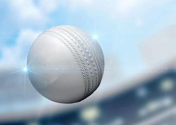 White Cricket Ball Against Blurred Stadium